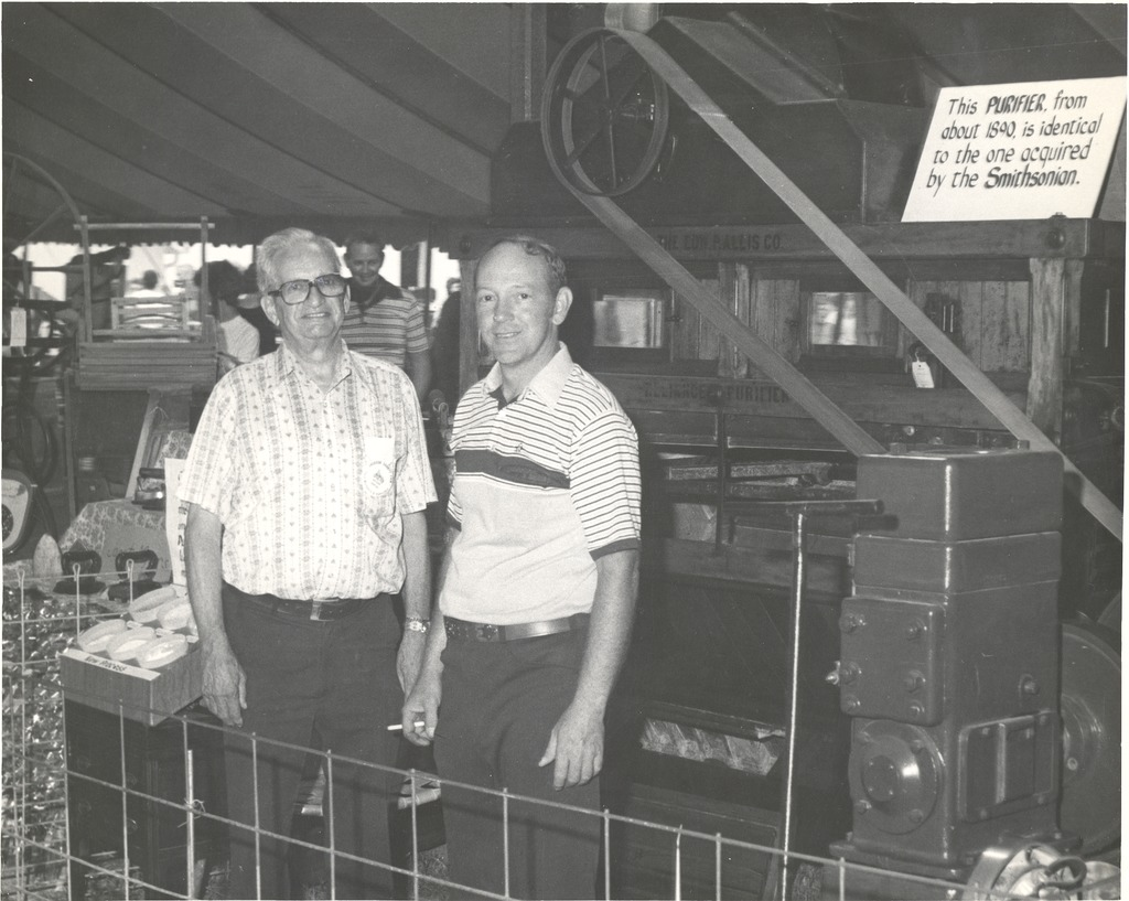 "Picture taken at Jackson Co. Fair 7/27-8/2, 1980, Edward Allis Purifier, Glenn Bleile and John H. ""Butch"" Robertson in the Antique Display tent with the 1890 Purifier, donated to the Smithsonian by the Robertson Corp."