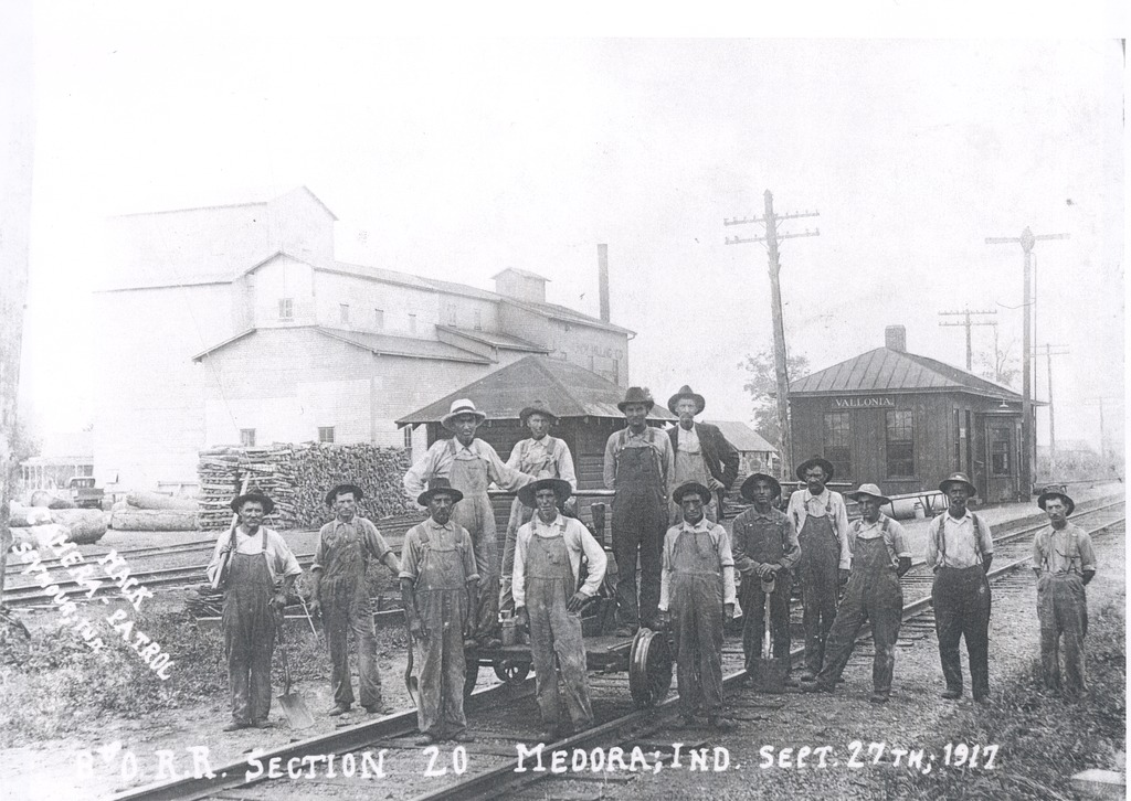 B and O RR Track Maintenance Section Crew from Medora, IN. Photographed at Vallonia (their east limit). In background: L. L. Bundy Milling and the Vallonia, IN B and O Railroad Depot. Standing on ground (L-R): Frank Weddle, Charles Harris, Henry Harris, Billy Coose, Newt Woods, Charlie (Big Foot) Weddle, Roy Weddle, Emmet (Ham) Davis, Bill Pearcy, Albert (Con) Pray. On track car (L-R) Dan Poore, Ash Gardner, foreman: Frank McKinney, and T.J. Richards. - from Paul Carr, bw 7.11x10.48