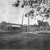 Street scene in Seymour with horse and buggies, note the brick street. Warehouse of Stanfield-Carlson Hardware Co. on corner.