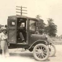 Man driving truck, woman in the foreground. about 1920