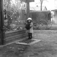 Southeast corner of Walnut and Brown Streets. Girl holding a muff outside of a store at Christmas time, possibly in the late 1890s.