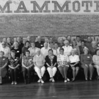 Group in front of Mammoth sign on the brick wall, 6/19 issue, Paul Jewett photo, Seymour, - from the Brownstown Banner, 7.06 x 4.94, bw