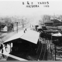 B and O freight yards, Medora, IN. View is looking west along B and O track. The depot is in the foreground, auto-livery across tracks on left. Frank Davis General Store is in background, right of center. Hamilton Hardware and Woolery Hotel are to the right. Side track comes in behind the B. and O. from the east and exited to the west where Perry Street crosses the railroad. - from Paul Carr, 6 1/2 x 4 1/2, bw.